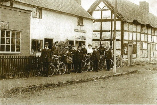 12 Postmen outside the old Post Office (now Greycote) next to Longford Cottage (now Markham's garage). Dunn's shoe shop on far left